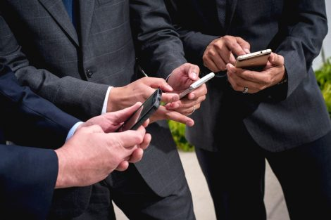 Chest-down photo of three people using cellphones