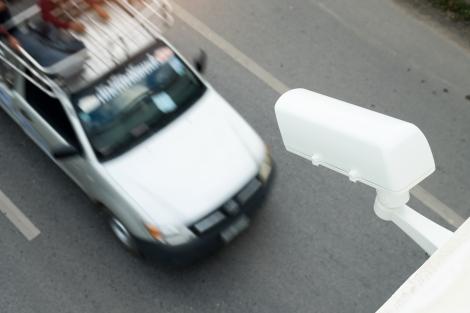 Image of a surveillance camera capturing a van driving past